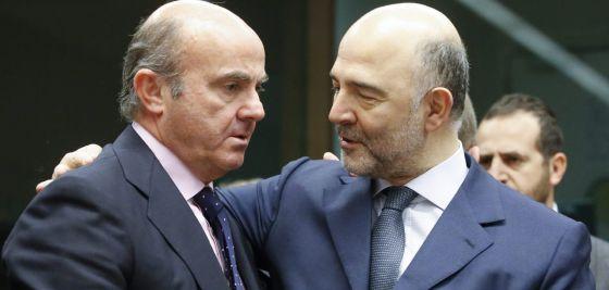 El ministro Luis de Guindos (i) conversa con el comisario europeo Pierre Moscovici