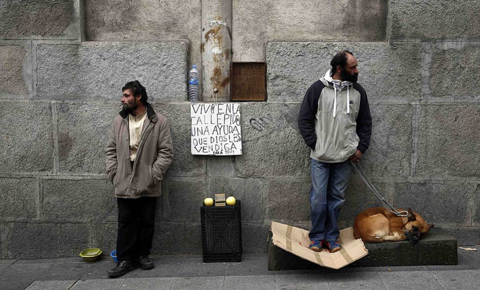 Two homeless men on the street in Madrid.