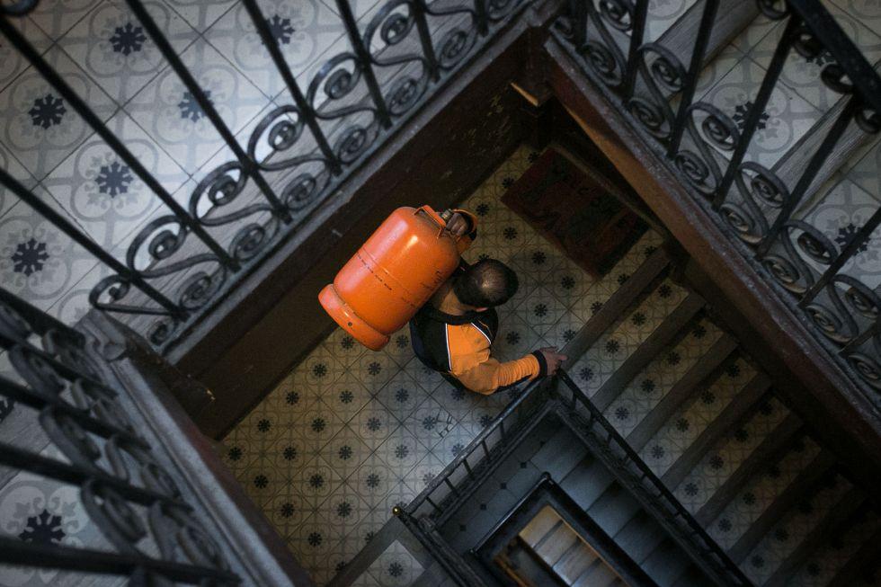 Un butanero sube una bombona a un piso de Barcelona.