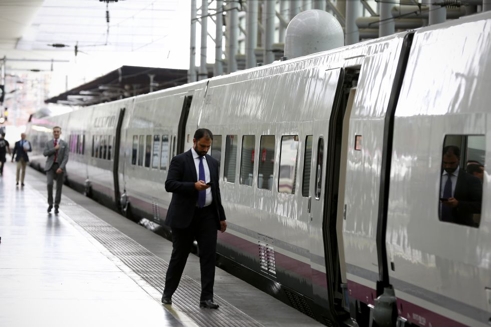 Un pasajero mira el móvil antes de entrar en un tren AVE