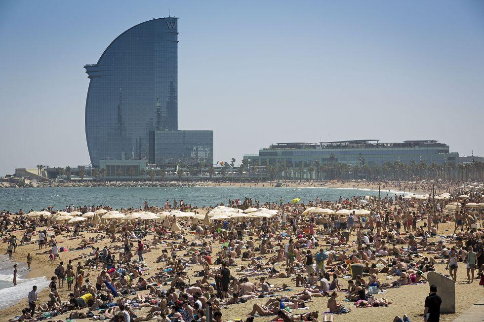 La playa de la Barceloneta abarrotada con el hotel Vela al fondo