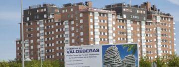 Cartel publicitario delante de una promoción de viviendas en régimen de cooperativa en Valdebebas (Madrid).