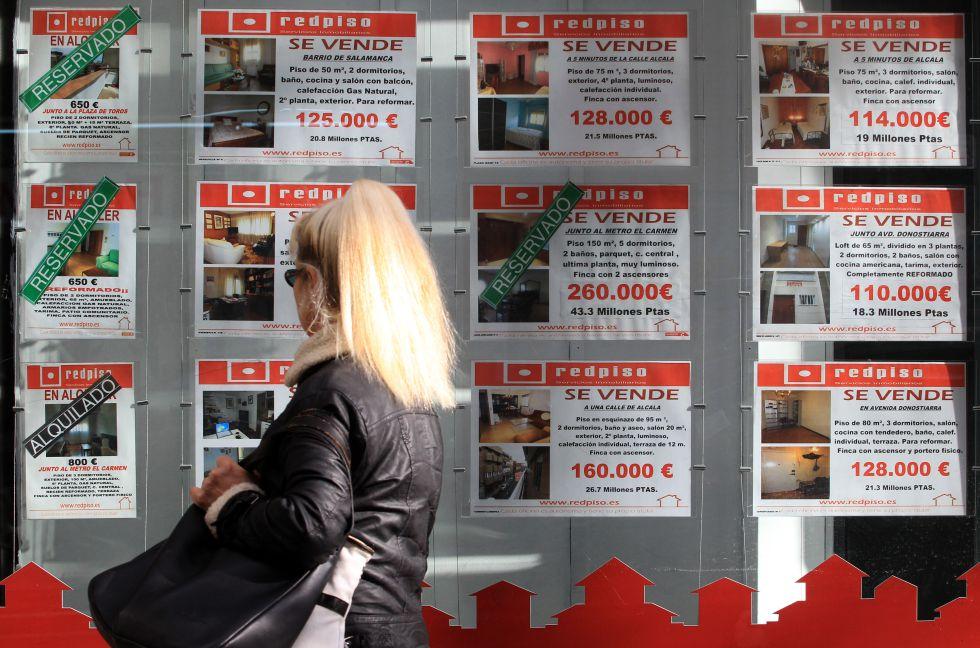 Carteles con pisos en venta en una oficina inmobiliaria en Madrid.