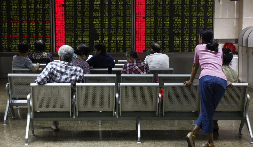 Varias personas comprueban la evolución de la bolsa de Shangái en Pekín (China).