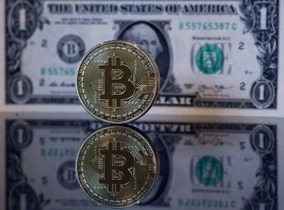 Un 'bitcoin' junto a un dólar.