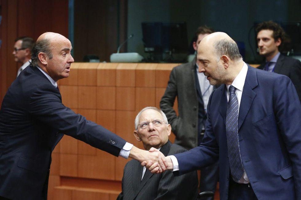 Luis de Guindos, estrecha la mano del comisario Pierre Moscovici en presencia del ministro alemán de Economía, Wolfgang Schaeuble.