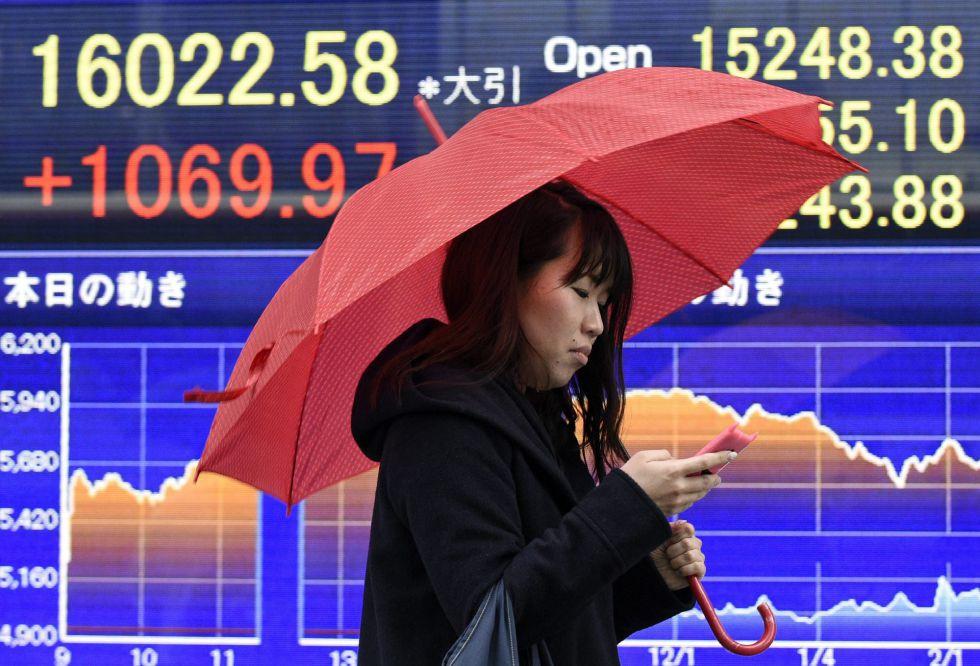 Una mujer camina junto a una pantalla con información bursátil en Tokio