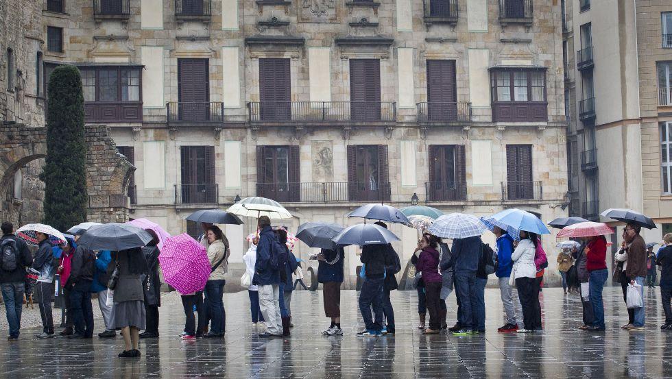 Turistas paseando por Barcelona durante una lluviosa jornada de vacaciones de Semana Santa.