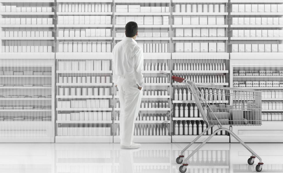 Un hombre vestido de blanco mira estantes blancos.