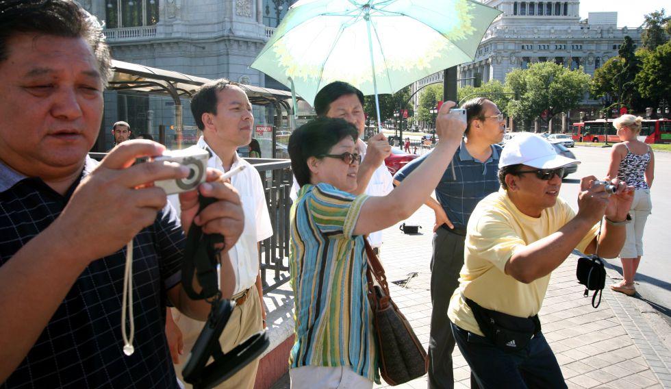 Turistas orientales (posiblemente chinos), en la Plaza de la Cibeles de Madrid.