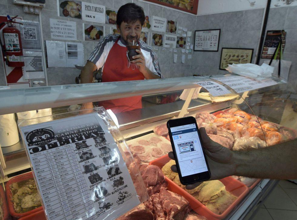 Un cliente comprueba con su móvil los precios de una canicería.