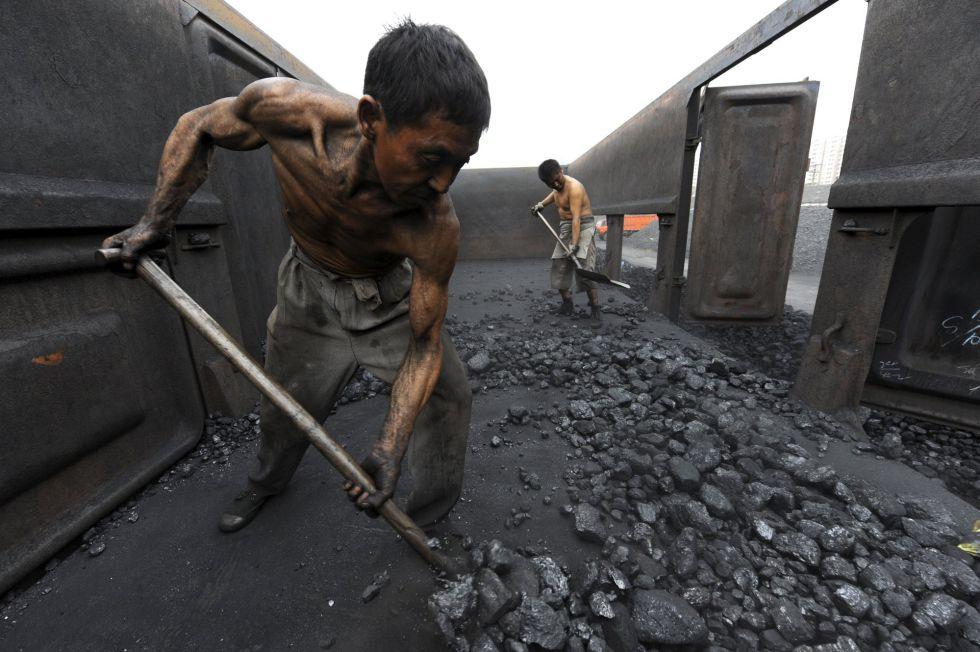 Dos trabajadores descargan carbón en un almacén en la estación de ferrocarril de Hefei, en la provincia china de Anhui.