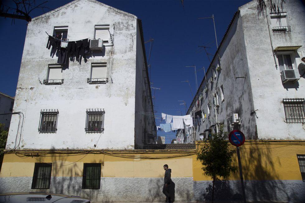 Un hombre camina frente a un edifico del barrio de 'Los Pajaritos' de Sevilla