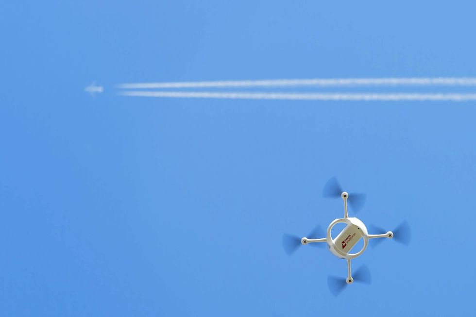 Un dron de reparto porta un paquete bajo la estela de un avión comercial.