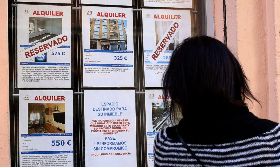 Una mujer mira anuncios de viviendas en una inmobiliaria