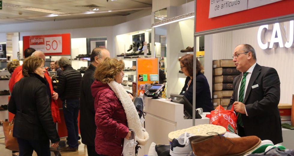 Varias personas realizan compras en un centro comercial.