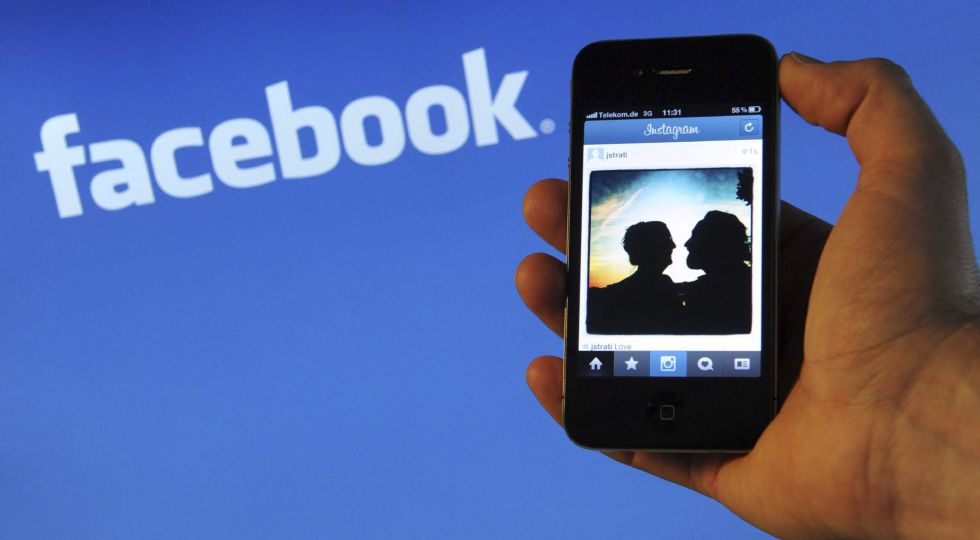 Un teléfono inteligente con el logo de facebook detrás.