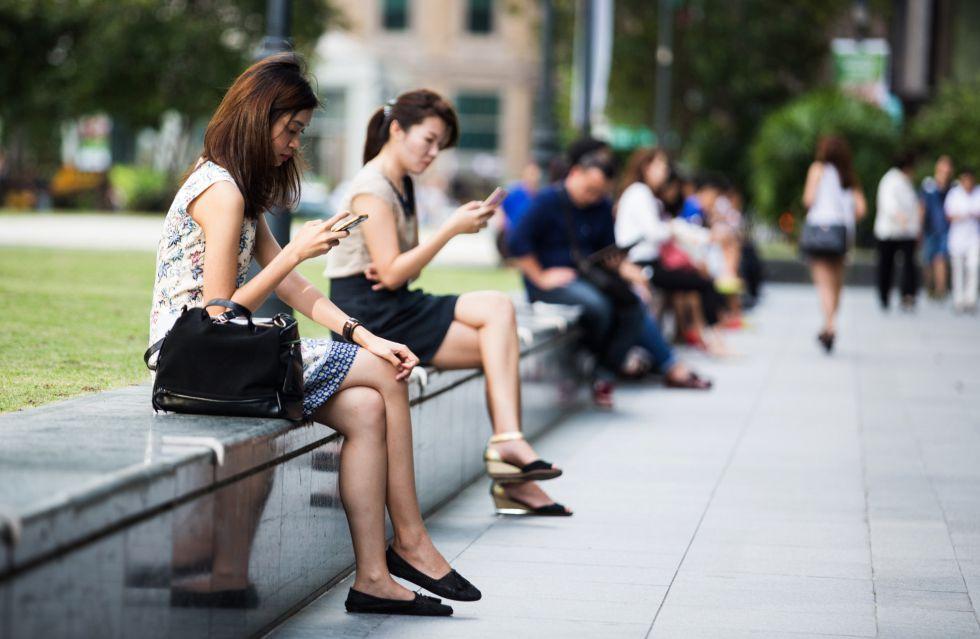 Mujeres navegando con sus móviles, en Singapur.