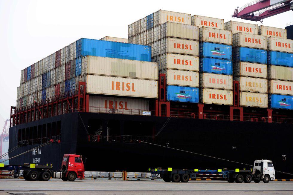 Varios camiones transportan contenedores en el puerto de Qingdao, en la provincia china de Shandong.rn
