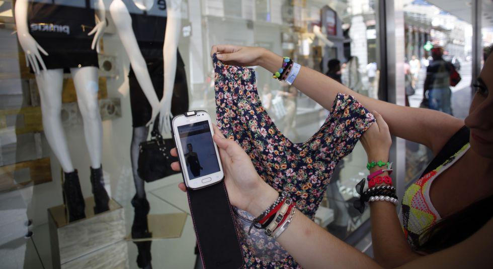 Dos mujeres jóvenes fotografían con sus móviles el escaparate de una tienda de ropa, en una calle de Madrid.