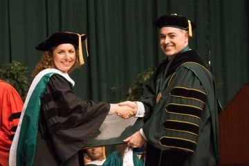 Cabrera entrega un diploma a una de las graduadas por la George Mason en 2012.