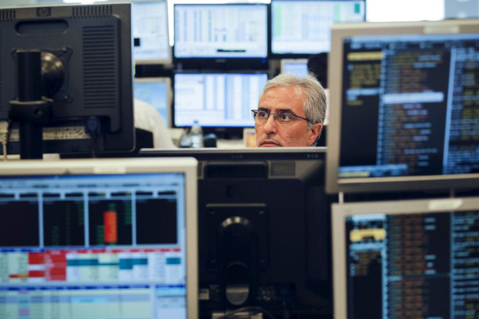 Un empleado de Ahorro Corporación, entre varias pantallas de Bloomberg.