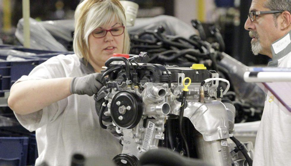 Una trabajadora de una cadena de montaje coloca piezas en un motor.
