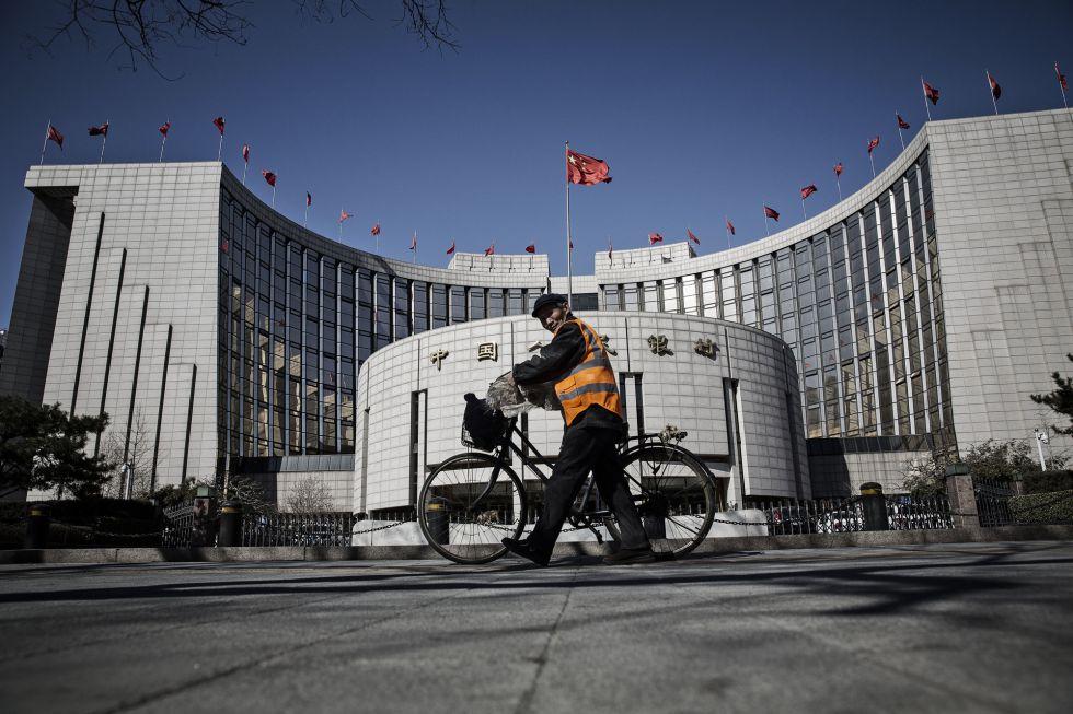 Un hombre pasa por delante de la sede del Banco Popular de China, en Pekín.