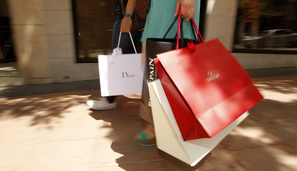 Dos turistas con bolsas de marcas de lujo en Madrid.