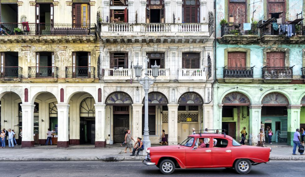 Un coche en el malecón de la Habana (Cuba), frente a unas casas.