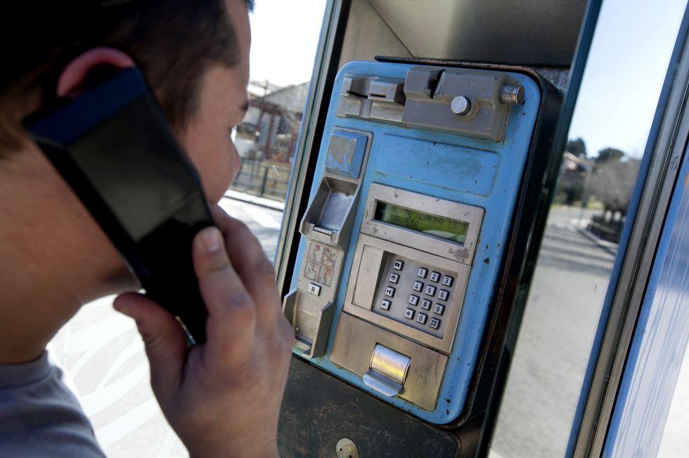 Un joven utiliza una cabina de teléfono en Madrid.
