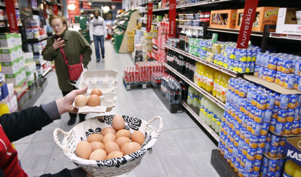 Huevos a granel y sección de bebidas incluyendo refrescos en un hipermercado.