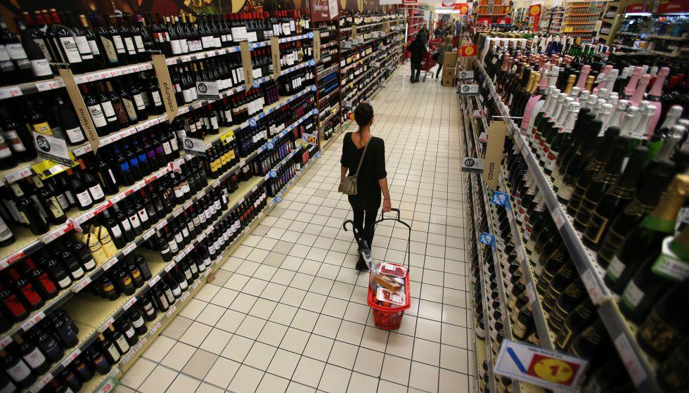 Una mujer con su cesta en la sección de vinos de un hipermercado.