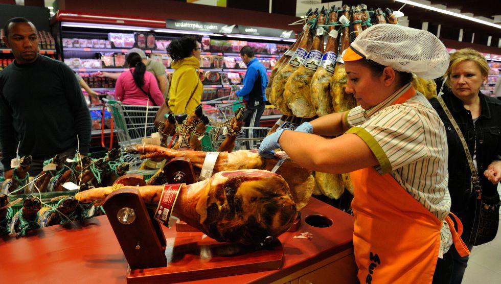 Una empleada cortando jamón en un supermercado.
