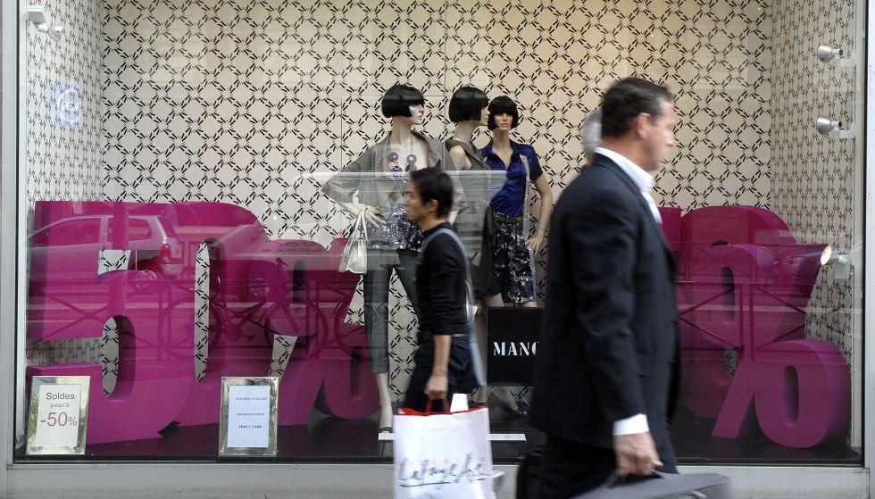 Dos consumidores andan frente a una tienda de moda en París (Francia).