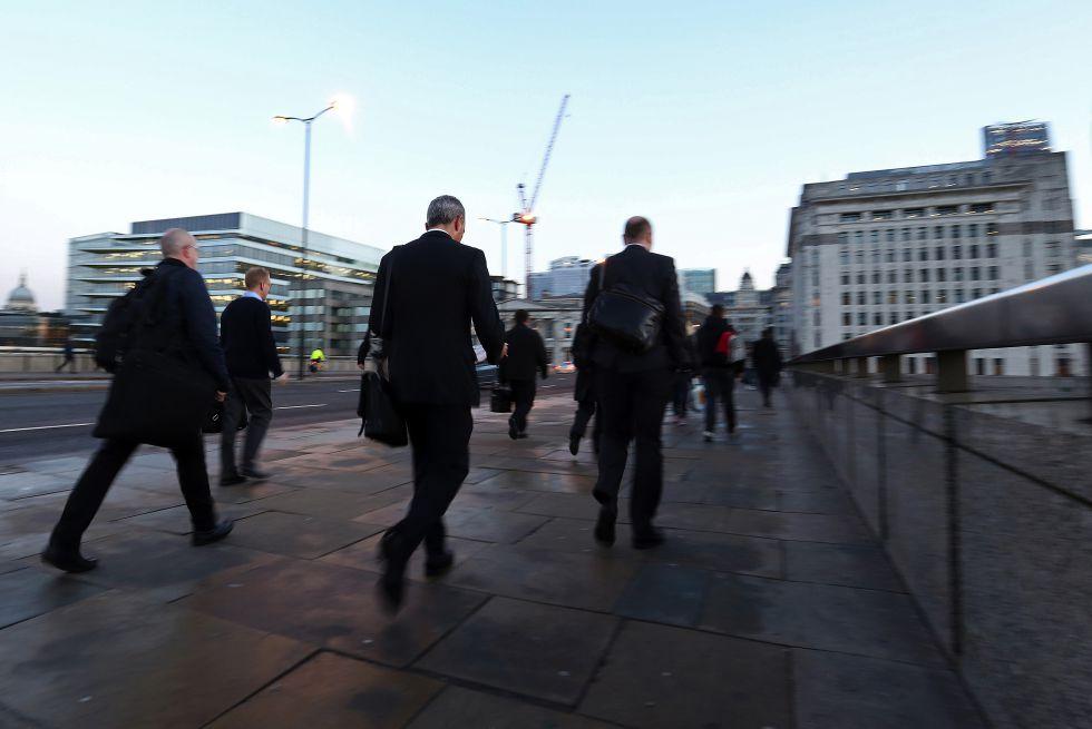 Varias personas cruzan el puente de Londres en dirección hacia a la City, el distrito financiero de Londres