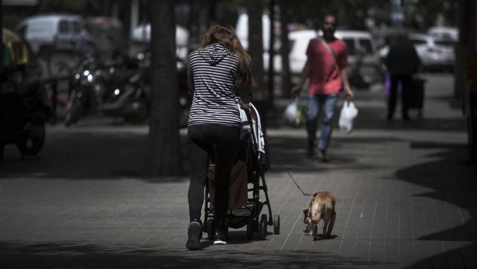 Una mujer pasea a su bebé por las calles de Barcelona.