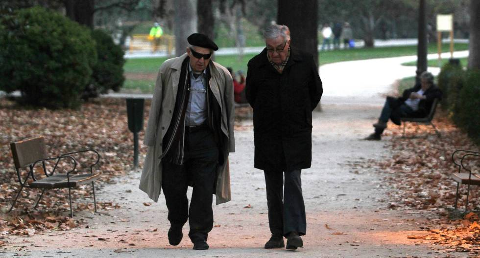 Dos personas mayores caminan por un parque en Madrid.
