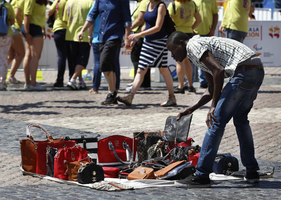 Un vendedor ambulante con una muestra de bolsos falsos.