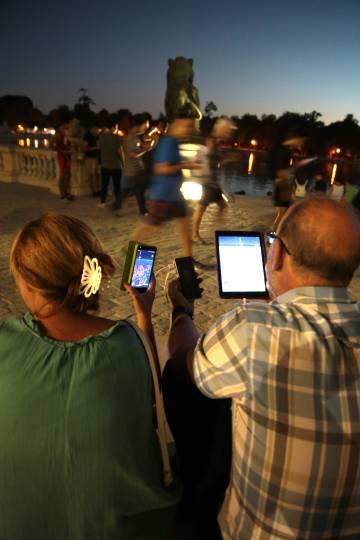 Dos personas juegan a Pokémon Go con sus dispositivos conectados a una única batería portátil.
