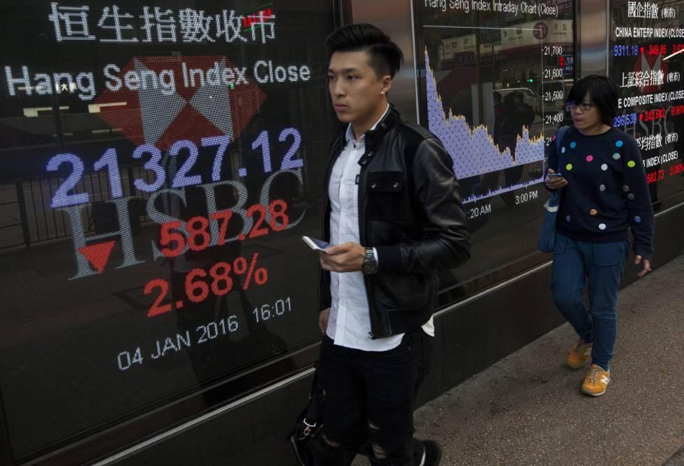 Peatones caminan junto a pantallas que muestran información bursátil en Hong Kong (China).