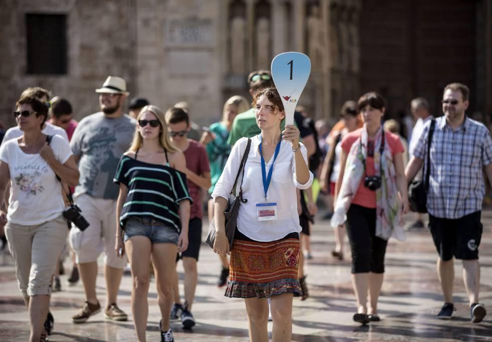 Un grupo de turistas sigue a su guía por el centro histórico de Valencia