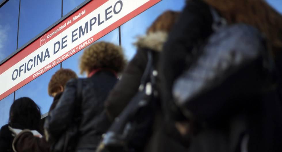 Mujeres esperan ante una oficina de empleo.