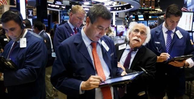 Corredores de Bolsa realizan su trabajo en el parqué de Nueva York