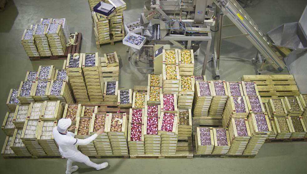 Una trabajadora de la fábrica de elaboración de dulces 'Aromas de Medina', junto a cajas de mantecados.