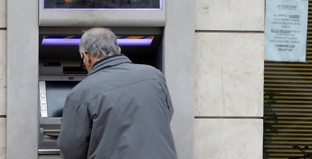 Un hombre retira efectivo de un cajero automático.
