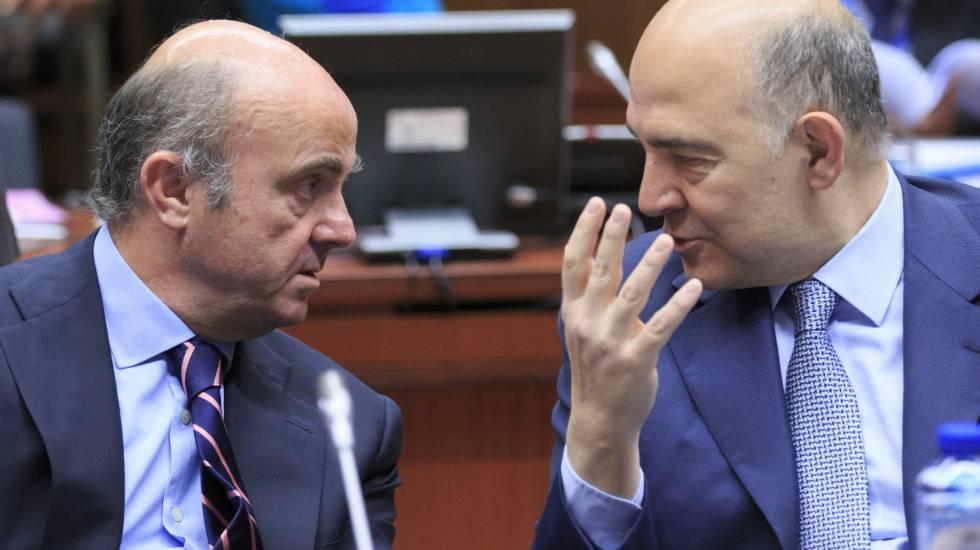 El ministro de Economía, Luis de Guindos, conversa con el comisario europeo de Asuntos Económicos y Financieros, Pierre Moscovici.