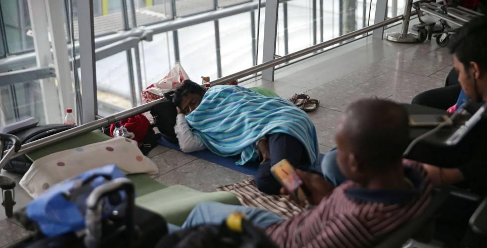 Un pasajero descansa en el suelo, en la terminal 5 del aeropuerto de Heathrow (Londres), el lunes.