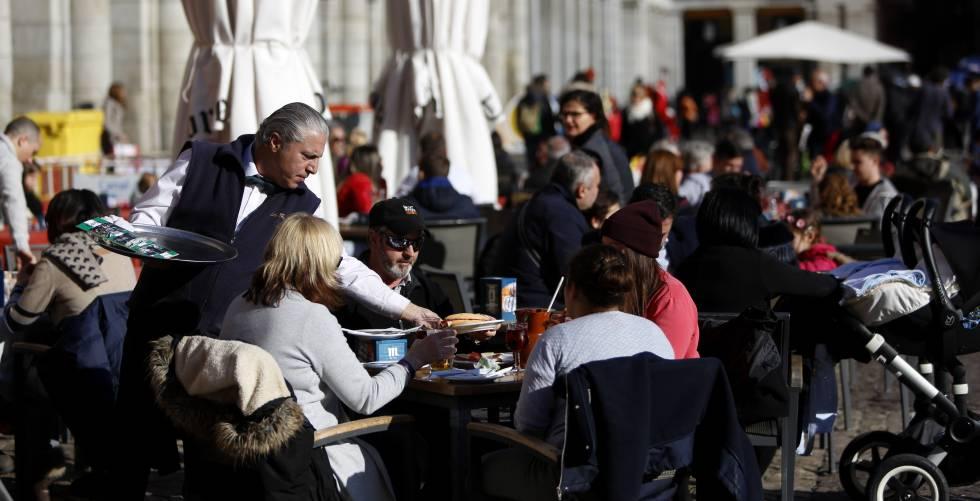 Un camarero sirviendo a unos clientes en la Plaza Mayor de Madrid