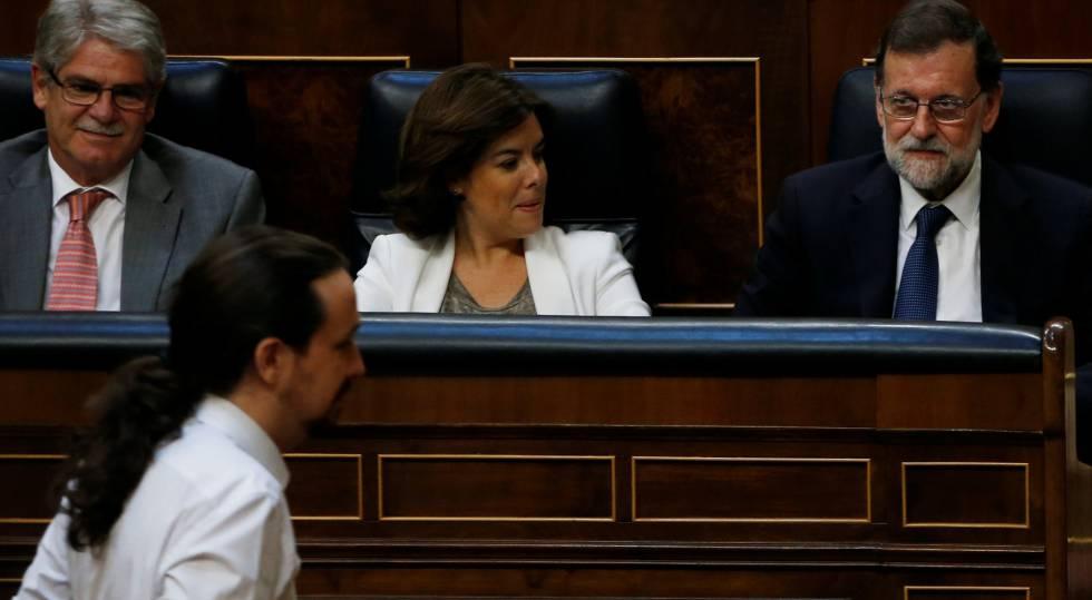 Pablo Iglesias pasa junto al escaño de Mariano Rajoy